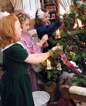 From left, Isabella Stading, Halle Blais and Leah Klammer, dressed as Tacy, Tibb and Betsy, decorate a Christmas tree in Betsy's House during the Betsy-Tacy Society's Victorian Christmas party Saturday.