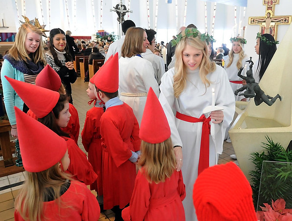 Pat Christman<br /> Attendant Emily Albrecht talks with the St. Lucia children after Thursday's Festival of St. Lucia at Gustavus Adolphus College.