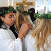 Pat Christman<br /> Attendant Haley Coller removes wax from St. Lucia Christina Swenson's hair after the Festival of St. Lucia Thursday.