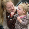 Maddy Schultze holds her daughter Rosie Schultze, 2, as she shook a bracelet of jingle bells that were handed out by Santa Claus at the Blue Earth County Library on Saturday. Santa played the guitar and sang Christmas songs at the event that was free and open to the public. Photo by Jackson Forderer