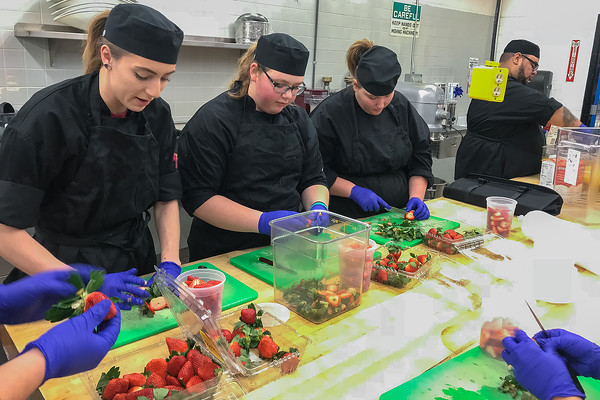 From left, Hannah LaCroix, Paige Thomas and Katlyn Johnson, students in South Central College's culinary program, prepare strawberries for a sample to be served later in the day at Hy Vee. Photo by Deanna Narveson
