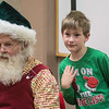 Charles Winiarski, 6, poses for a photo with Santa Claus after Santa sang Christmas songs with the audience at the Blue Earth County Library on Saturday. Photo by Jackson Forderer