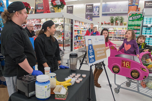 Andrea Fulsom (second from left), 4, gets excited as she sees samples of a chocolate protein smoothie prepared by South Central College culinary students Dominic Sprung (left) and Hannah Groth at Hy Vee Hilltop on Friday. SCC students prepared five different food samples to give away at Hy Vee to promote the school's culinary program. Photo by Jackson Forderer