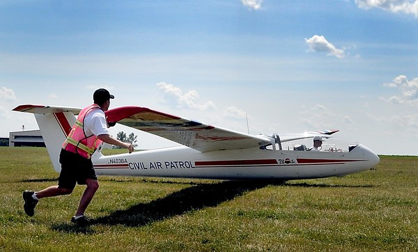 A Civil Air Patrol cadet runs with the wing of a glider as it is towed aloft Thursday. File photo