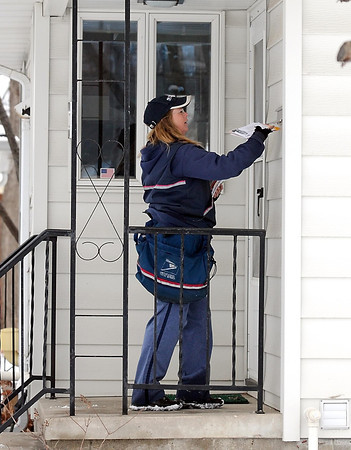 Letter carrier Kim Roy delivers mail along her route Wednesday in Mankato.