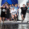 The team Walsh's Warriors leaps into Hallett's Pond during Saturday's Polar Plunge.