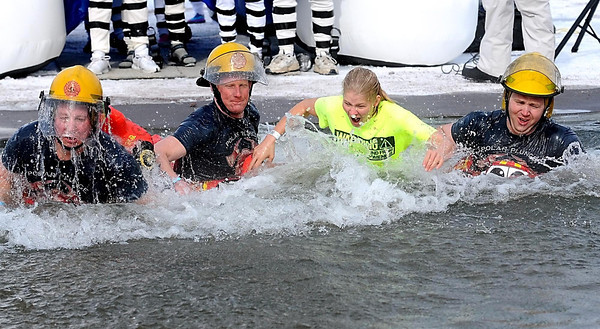 Members of the North Mankato Fire Department emerge from the chilly waters of Hallett's Pond in St. Peter during Saturday's Polar Plunge.