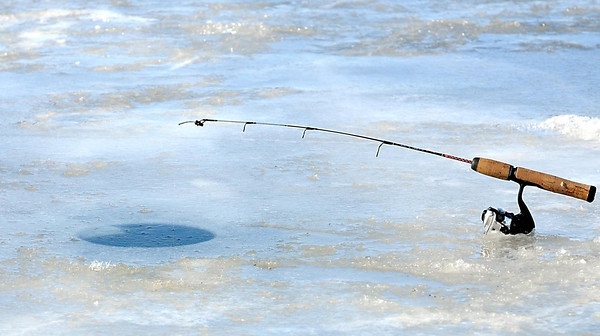An ice fishing rod sits at the edge of a flooded hole during Saturday's Big Bobber Ice Fishing Contest.