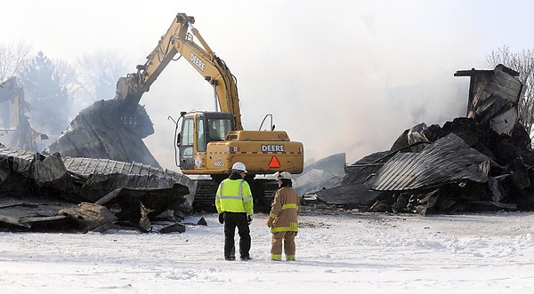 Pat Christman<br /> Workers use equipment to take the remnants of the building down to finish putting out the fire Saturday afternoon.