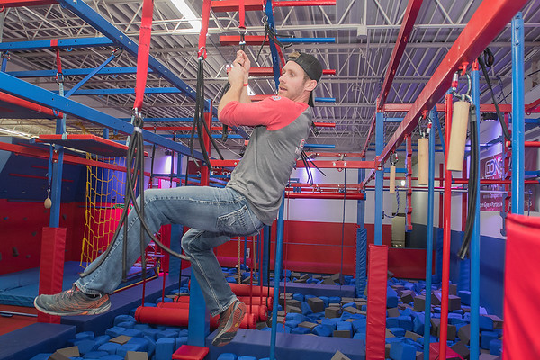 Mitch Pajcic holds onto bungee cords as he swings through an obstacle at the Conquer Ninja Warrior gym on Wednesday. Pajcic, an employee at the gym, has competed on the TV show American Ninja Warrior, from which many of the obstacles of the gym are modeled after. Photo by Jackson Forderer