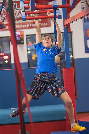 Noah Femrite (11) climbs across a tilted monkey bars at the Conquer Ninja Warrior gym in Mankato on Wednesday. The gym features real obstacles from the TV show American Ninja Warriors and tests one's strength, balance and agility. Photo by Jackson Forderer