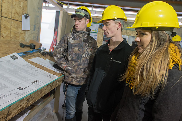 Founding board chair of the Ace Mentoring Program Leah Roue (right) looks over blueprints of the Eide Bailly Center with Hank Johnson (left) and Tanner Stier (center) during the program's tour of the building on Tuesday. Photo by Jackson Forderer