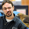 University of Minnesota Raptor Center's Mike Billington winks to illustrate how the red-tailed hawk he's holding sees after its injury. The hawk lost the use of its left eye and is now a permanent resident at the center.