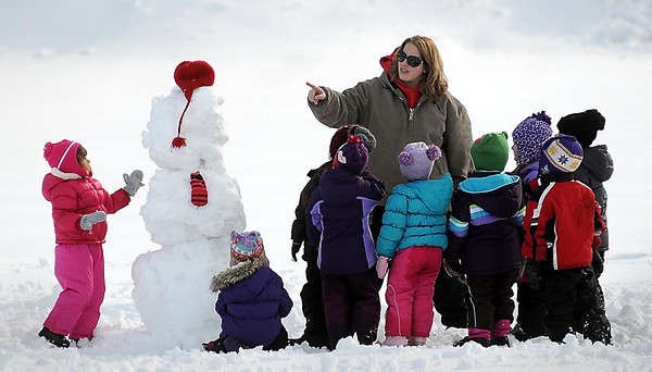 John Cross<br /> Jessica Busack, a teacher at Jesus Loves Me Learning Center in North Mankato, and her charges admire the snowman they built during Tuesday's 40 degree weather. The fat, white fellow might be hanging around for a while with a forecast calling for more cold weather by this weekend.