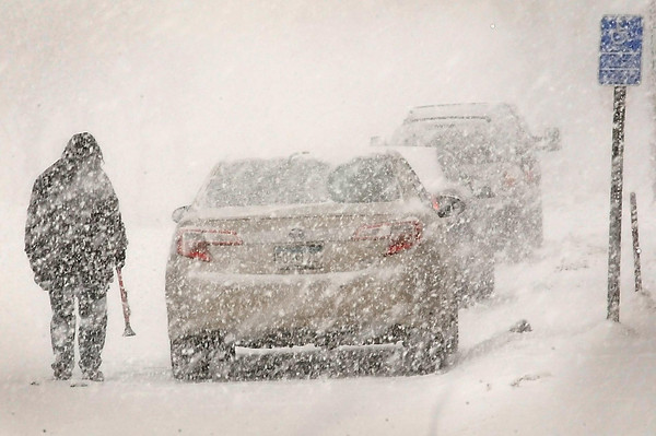 John Cross<br /> A motorist is caught in a swirl of snowflakes Saturday as he cleans snow from his vehicle in downtown Mankato.