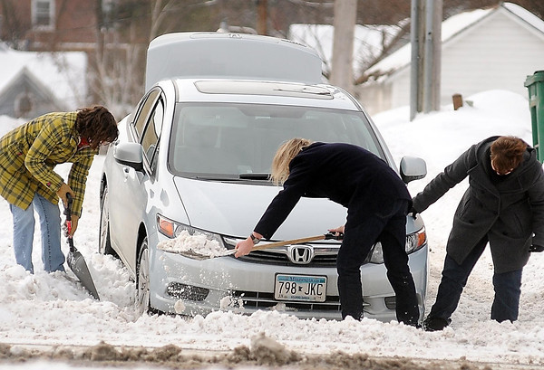 John Cross<br /> Shovelers work to free a car that got stuck in a snowbank along Cherry Street on Monday. The heavy, wet snow for a time made travel difficult on Mankato side streets until plows could get them cleared.