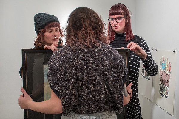 Olivia Sirek (center) holds a painting up for Dana Sikkila (left) and Kathryn Mast as they prepare to hang the artwork on the wall at the 410 Project for the annual juried exhibition which opens on Feb. 16. Photo by Jackson Forderer
