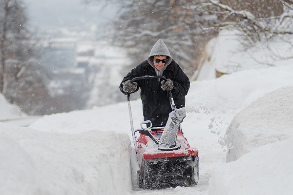 """Mary Hennegar blows snow off of her sidewalk atop Main Street hill on Wednesday afternoon. Dave Hennegar said about the snowfall, """"Oh well, it's Minnesota, there's not much you can do about it. You've gotta live with it."""" Photo by Jackson Forderer"""
