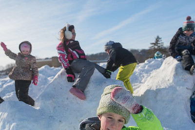 Brandon Stafford, 7, adjusts his hat as he and other students from the Jesus Loves Me Learning Center play on piles of snow outside of Monroe Elementary School in North Mankato. Photo by Jackson Forderer