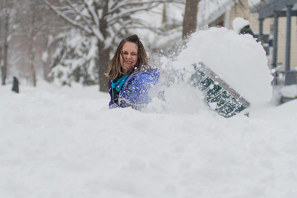 """Jerusha Zimmerman shovels snow onto an already tall pile of snow along Nicollet Avenue in North Mankato on Wednesday. """"It's almost like you have to throw it over your head to get it to go anywhere,"""" said Zimmerman while helping her neighbor shovel. Photo by Jackson Forderer"""