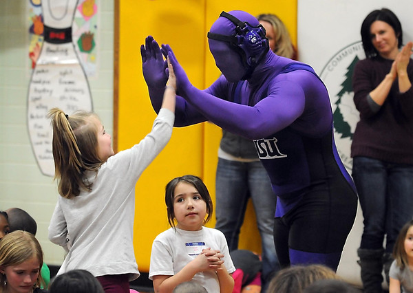 Kennedy Elementary School first grader Kristy Paulson gets a high five from Minnesota State wrestler C.J. Hayes dressed in a purple man suit during the school's Jump Rope for Heart event. Paulson raised $410, the most in the school, for the American Heart Association.