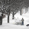 John Cross<br /> A resident along Lewis Street in the Lincoln Park neighborhood clears snow from his vehicle during Friday's storm.