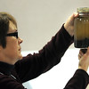 Pat Christman<br /> Benson High School teacher Ruth Ahrndt examines a jar of soil and water during a demonstration by the University of Minnesota Monarch Lab at the Minnesota Conference on Science Education in Mankato.