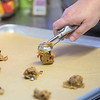 Lisa Phillips puts a batch of vegan chocolate chip pumpkin cookie dough onto a baking sheet at the Blue Skye Farms kitchen on Friday. Phillips bought the kitchen a year ago when she asked the Holy Rosary Elementary School if the old kitchen was available to be purchased. Photo by Jackson Forderer