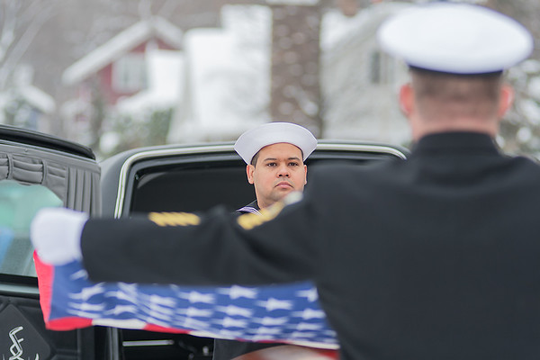 Chief Chris Stauffer, right, and Logistics Specialist Second Class Richard Walz begin the flag folding ceremony at Victor Paradis' funeral on Saturday. The folded flag was given to Lucille Paradis, who married Victor in 1946 following World War II. Photo by Jackson Forderer