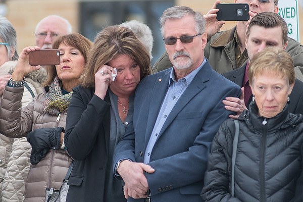 Molly Loe (second from left) comforts Tom Paradis, son of the late Victor Paradis, while wiping a tear from her eye as members of the military honored Victor Paradis' service outside of St. Joseph the Worker Catholic Church in Mankato. Photo by Jackson Forderer