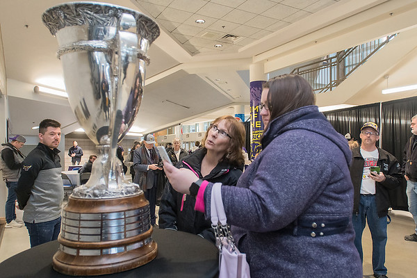 Megan Vossen (right) and Sharon Vossen (center) get up close and personal with the Macnaughton Cup at a celebration event for the Minnesota State Maverick's men's hockey team held on Tuesday at the Verizon Center. The trophy, which goes to the WCHA conference champion, has gone to MSU the past four out of five years. Photo by Jackson Forderer