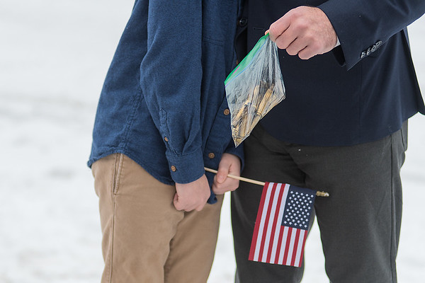 Jonah Paradis (left), 11, leans into his dad Seth Paradis for a hug at Victor Paradis' military honors following his funeral at St. Joseph the Worker Catholic Church in Mankato. Seth is holding a bag of shells from the 21-gun salute for his grandfather Victor. Photo by Jackson Forderer