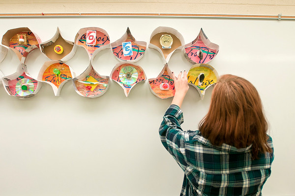 Rachel Sorenson puts up a piece of a collage made participants of Studio 3:45 at South Central College on Thursday. The final session in the workshop series for area high school students is on April 20. Photo by Jackson Forderer
