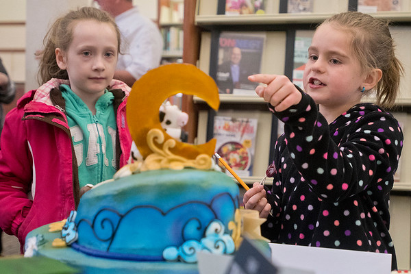 Peyton Carstensen (right) points to the cow in the moon while looking at a cake called Bedtime Stories with Brynley Bellig at the Edible Book Festival held at the North Mankato Public Library. The Bedtime Stories cake was submitted by Hy Vee and won the professional category. Photo by Jackson Forderer