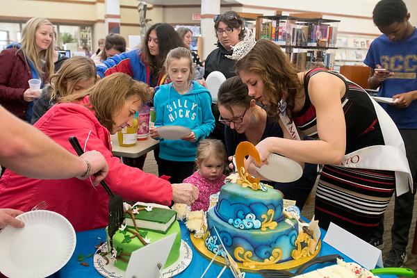 Miss Mankato Taylor Sexton (right) helps serve pieces of cake to those in attendance at the Edible Book Festival held at the North Mankato Library on Saturday. The cake on the left, which won the people's choice award, was made by Megan Cherney and called My Precious based on the Lord of the Rings. The cake on the right was made by Hy Vee and called Bedtime Stories. Photo by Jackson Forderer