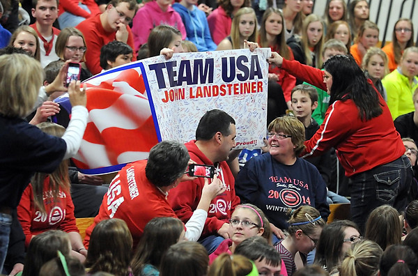 Pat Christman<br /> Steve and Cheryl Landsteiner, parents of Olympic curler John Landsteiner, sit in front of a banner signed by the students at Maple River Schools during a pep fest Friday at the high school. The Landsteiners will take the banner with them to Sochi next week.