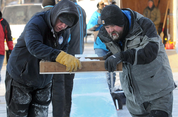 Pat Christman<br /> Ice sculptors Joe Christenson, left, and Adam Scholljegerdes use a plane to smooth the top of a row of ice blocks while making a sculpture for the Waseca Sleigh and Cutter Festival Thursday.