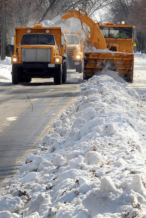 John Cross<br /> A North Mankato rotary blower chews its way down a windrow of snow on Range Street on Tuesday. City crews are trucking the snow that has been piled along the curb by plowing operations over the course of the winter to another site.