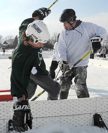 Pat Christman<br /> A pond hockey player falls over the boards during a game Saturday.