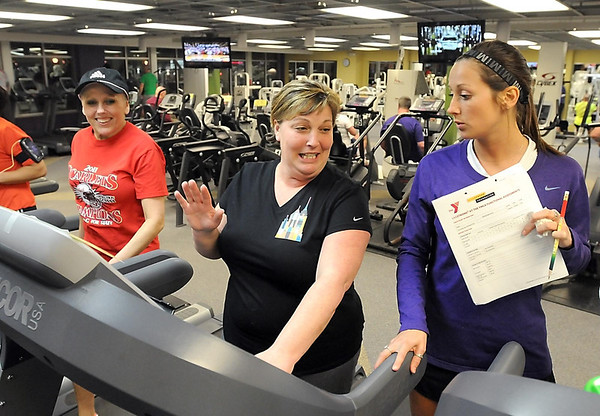 Pat Christman<br /> Livestrong volunteer Kristina Gelecki, right, helps class participants Mary Reichel, center, ad Shelly Rigdon set up treadmills during a workout at the Mankato YMCA.
