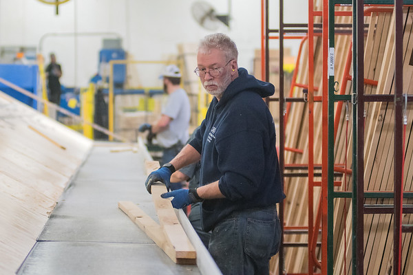 Dave Keene picks up a piece of wood that will be sorted out for a specific product at the Elkay Wood Products plant in New Ulm. Photo by Jackson Forderer