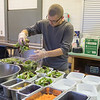 Jack Jennings of Bea's Kitchen picks up a handful of lettuce as he prepared a salad called the Buddha Bowl in the kitchen at Holy Rosary Elementary School. Photo by Jackson Forderer