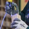 An Elkay Wood Products employee applies glue to a piece of wood at the company's plant in New Ulm. The plant has a blue light that illuminates the glue, making it easier for employees to see. Photo by Jackson Forderer