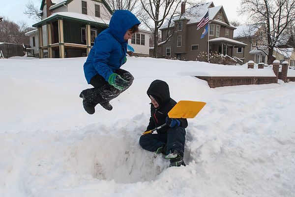 Omar Haque (left), 7, jumps into a hole dug out by Calin Lassonde, 6, as the two played in the snow on Thursday. Photo by Jackson Forderer