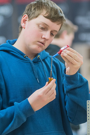 Brandon Krueger, 16, uses Loctite to lock a screw to a nut while working on his team's Vex Robotic at Mankato West High School on Tuesday. Photo by Jackson Forderer