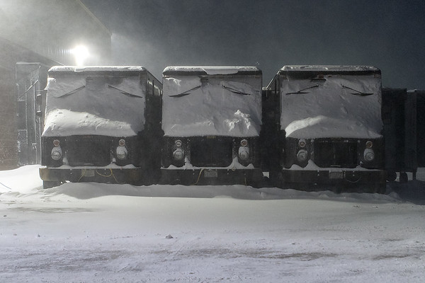 Three old UPS trucks bear the brunt of high winds blowing snow in North Mankato on Thursday evening. Photo by Jackson Forderer