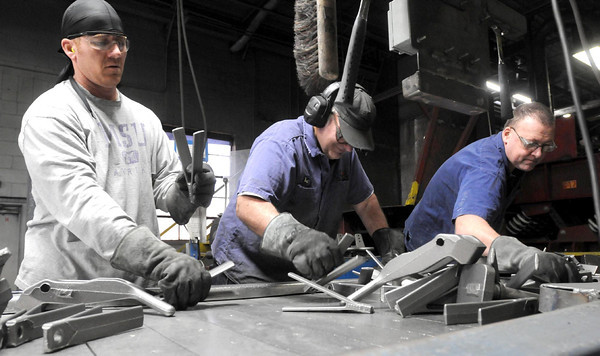From left, Mike Bequette, Bruce Blank and Ron Wagner inspect newly cast metal parts Thursday at Dotson Iron Castings in Mankato.