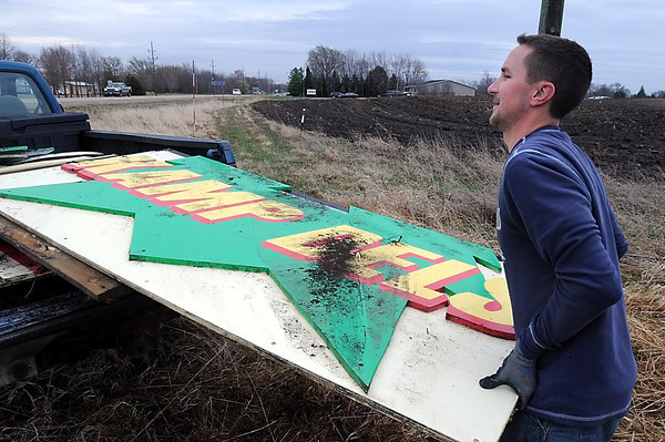 John Cross<br /> Dave Slechta of Waterville cleans up a sign along Highway 60 west of Elysian that was destroyed by strong winds Monday.