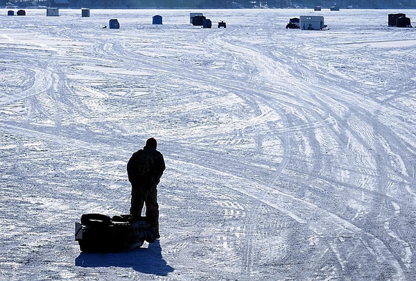 An ice angler hoofs it out to his Lake Washington fishing spot, shelter in tow. While recent cold weather has improved ice conditions on area lakes, Minnesota Department of Natural Resources officials are reminding outdoor enthtusiasts that ice is never 100 percent safe.