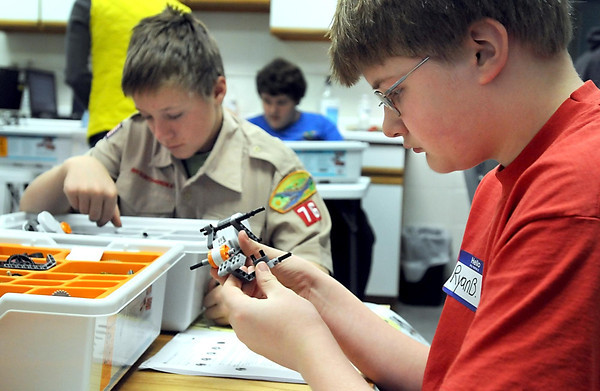 Boy Scouts Ryan Buendorf, foreground, and Jacob Bristol assemble robots during a robotics camp sleep in Friday evening at the Children's Museum of Southern Minnesota. Over the course of the evening, scouts learned about robotic sensors, assembly and programming on their way to earning their robotics badge.